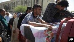 15일 이라크 바그다드에서 연쇄폭탄 공격으로 사망한 희생자의 시신을 가족들이 옮기고 있다.