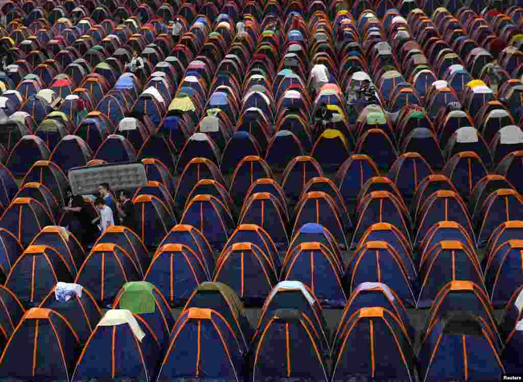 A man carries an inflatable mattress as he arrives at the camping area of the Campus Party event in Sao Paulo, Brazil.