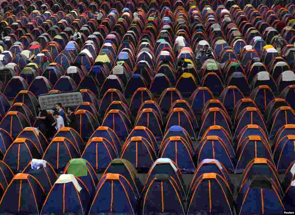 Brezilya'da düzenlenecek olan parti için, bir okul bahçesine kurulan çadırların yanından bir adam şişme yatak ile yürüyerek geçiyor.