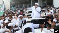 Ketua Front Pembela Islam (FPI) Rizieq Shihab (tengah) berbicara di hadapan para pendukungnya setelah tiba di Tanah Air dari Arab Saudi, di Bandara Soekarno-Hatta, Tangerang, Selasa, 10 November 2020. (Foto: AP)
