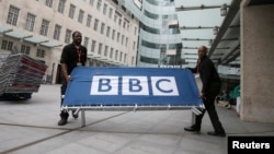 FILE - BBC workers place barriers near to the main entrance of the BBC headquarters and studios in Portland Place, London, July 16, 2015. Britain stepped back from cutting the size and scope of the BBC on May 12, 2016, after the publicly-funded broadcaster and some of its biggest stars had accused ministers of threatening the independence of the 94-year-old institution.