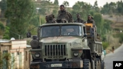 FILE - Ethiopian government soldiers ride in the back of a truck on a road leading to Abi Adi, in the Tigray region of northern Ethiopia, May 11, 2021.