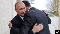 Presiden Rusia Vladimir Putin (kiri) memeluk tamunya Presiden Suriah Bashar Assad kota resor Sochi, Rusia, Senin (20/11).