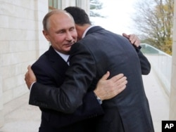 Russian President Vladimir Putin (L) embraces Syrian President Bashar Assad in the Bocharov Ruchei residence in the Black Sea resort of Sochi, Russia, Nov. 20, 2017.