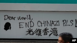 A man walks past a wall with the words 'Liberate Hong Kong- Dear World End Chinazi Please' in Hong Kong, Monday, Oct. 7, 2019.
