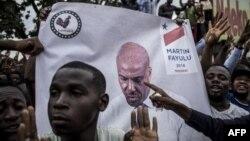 La police se tient devant les partisans du leader de l'opposition en République démocratique du Congo et candidat à la présidence, Martin Fayulu, alors qu'ils participent à une manifestation pour contester les résultats le 11 janvier 2019, à Kinshasa.