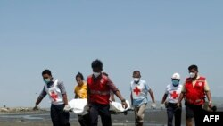 Members of the Myanmar Red Cross carry a dead body of a driver from a boat in Sittwe, Rakhine State