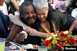Richard Brown (L) is hugged by volunteer Jane Johnson during Thanksgiving meal served to the homeless in 2013