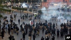 Pakistan police officers fire tear gas shell to disperse Shiite Muslims during an anti-U.S rally, when they tried to march toward the U.S. consulate, in Karachi, Pakistan, Aug. 27, 2017.