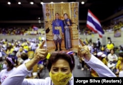 "A person holds a picture of Thai King Maha Vajiralongkorn with Queen Suthida as members of Thai right-wing group ""Thai Pakdee"" (Loyal Thai) attend a rally in Bangkok, Thailand August 30, 2020. REUTERS/Jorge Silva"