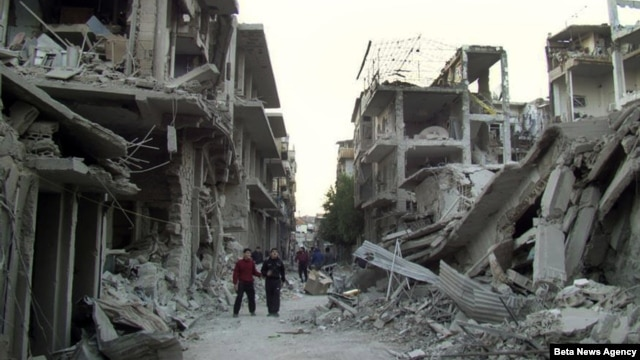 Syrian citizens walk in a destroyed street that was attacked on Wednesday by Syrian forces warplanes, at Abu al-Hol street in Homs province, Syria, Nov. 29, 2012.