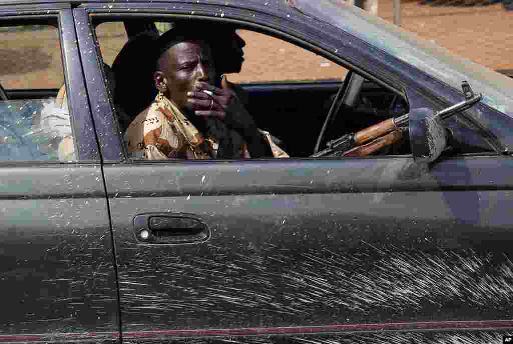 Armed men drive with thousands of Muslim residents from Bangui and Mbaiki fleeing the Central African Republic capital Bangui, Feb. 7, 2014.