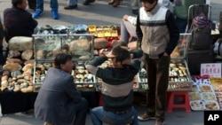 維吾爾人在北京一處戶外古玩市場賣玉。自從天安門發生汽車襲擊事件後,這些維吾爾人天天受到警察檢查。