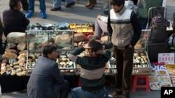Para pedagang batu giok dari Uighur menunggu pembeli di pelataran luar sebuah pasar di Beijing, China (30/10). Polisi setempat setiap hari memeriksa tanda pengenal para pedagang asal Uighur pasca ledakan mobil di Lapangan Tiananmen.