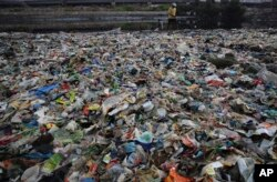 """A man walks on the shores the Arabian Sea, littered with plastic and other garbage in Mumbai, India, Monday, June 4, 2018. The theme for this year's World Environment Day, marked on June 5, is """"Beat Plastic Pollution."""" (AP Photo/Rafiq Maqbool)"""