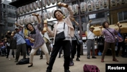 Elderly and middle-age people exercise during a health promotion event in Tokyo, September 2015. (REUTERS/Issei Kato)