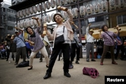 """Elderly and middle-age people exercise with wooden weights during a health event to celebrate Japan's """"Respect for the Aged Day"""" at a temple in Tokyo, 2015."""