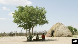 Two Basarwa women hide from the scorching sun in Metsiamenong, a remote village in the heart of the Central Kalahari Game Reserve, Botswana. (2007 file photo)
