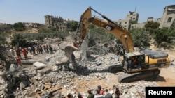 Warga Palestina berkumpul ketika tim SAR mencari korban di bawah reruntuhan sebuah rumah, yang menurut saksi mata hancur akibat serangan udara Israel, di Beit Lahiya di Jalur Gaza utara, 25 Agustus 2014.