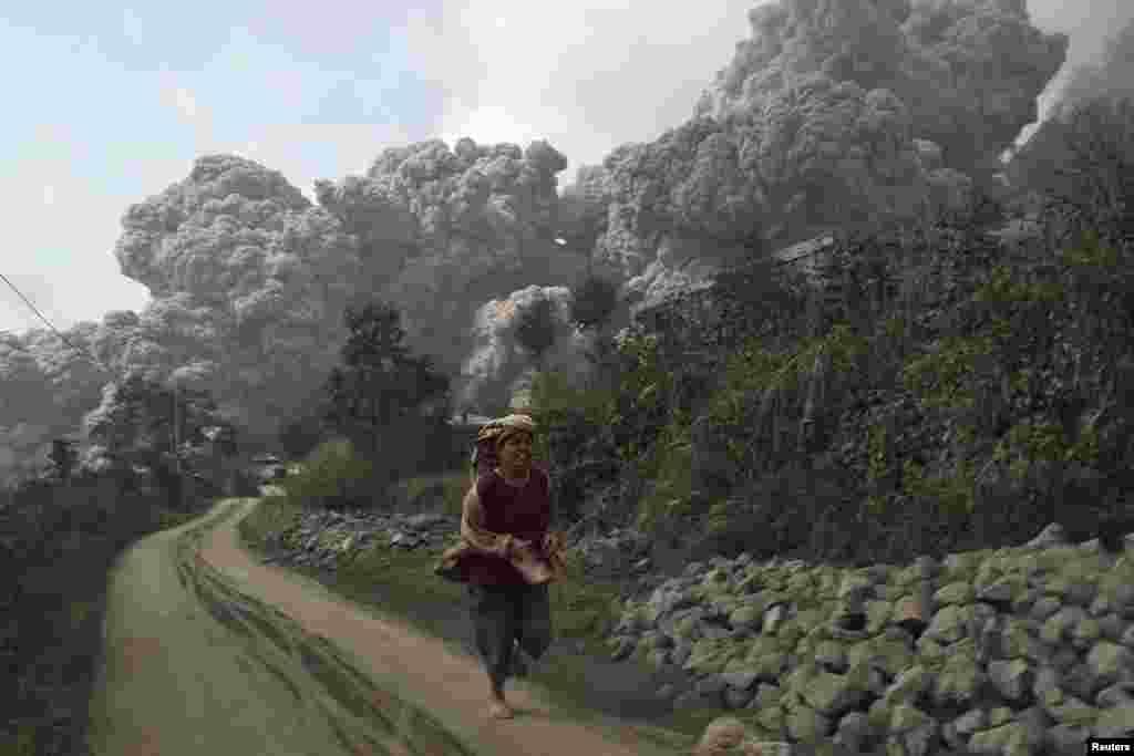 A villager runs as Mount Sinabung erupts at Sigarang-Garang village in Karo district, Indonesia's North Sumatra province.