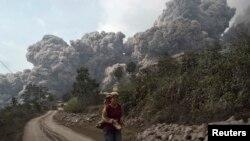 အင္ဒိုနီးရွား၊ Karo ခ႐ိုင္အတြင္း၊ Sigrang-Garang ေက်းရြာနားက Sinabung မီးေတာင္ ေပါက္ကဲြတဲ့ေနရာက ထြက္ေျပးေနတဲ့ ရြာသားတစ္ဦး။ (ေဖေဖာ္ဝါရီ ၁၊ ၂၀၁၄)