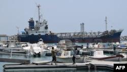 Les pêcheurs vérifient leur filet devant les navires amarrés dans le port de Fujairah le 2 juillet 2019 à l'est des Émirats arabes unis (EAU).