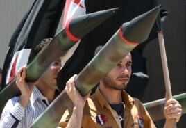 Two Lebanese men carry a fake missile to protest against the Israeli offensive in Gaza, as they take part in a sit-in, in front the United Nations headquarters, in downtown Beirut, Lebanon, July 13, 2014.