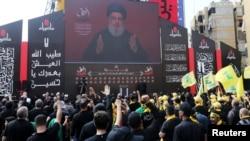 Pemimpin Hezbollah di Lebanon, Sayyed Hassan Nasrallah, tampak di layar saat perayaan hari Ashura di Beirut, Lebanon 10 September 2019. (Foto: Aziz Taher/Reuters)
