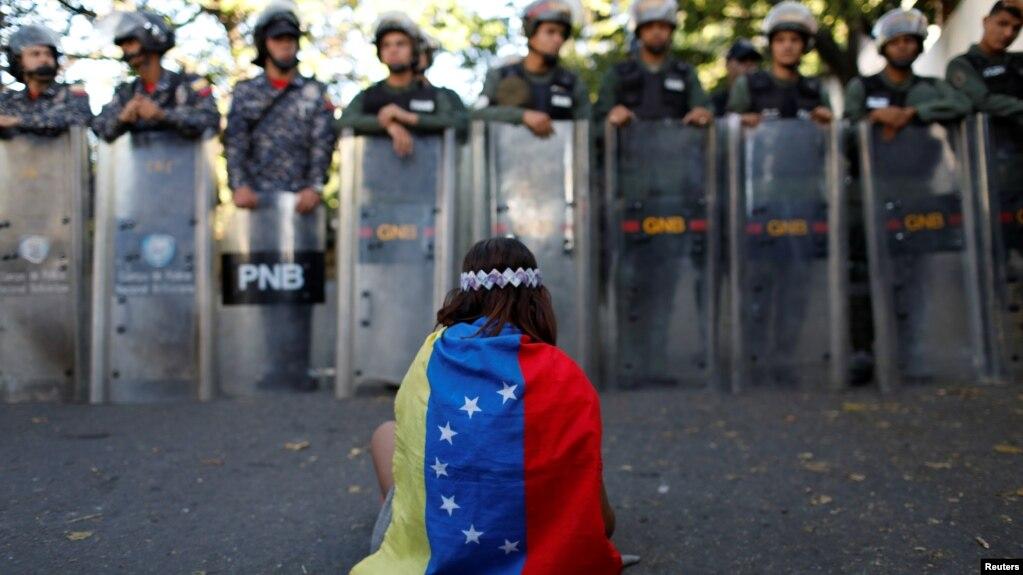 Una niña cubierta con la bandera de Venezuela se sienta en protesta frente a fuerzas de seguridad que bloquean el acceso a la morgue en Caracas de partidarios y dolientes del ex efectivo de seguridad Óscar Pérez, que se rebeló contra el gobierno del presidente Nicolás Maduro. Enero 20 de 2018.