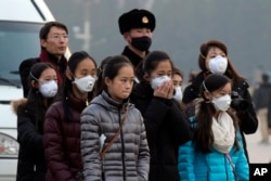 FILE - Young tourists wear masks as they stand near a Chinese Paramilitary policeman in Tiananmen Square in Beijing, China, Dec. 19, 2015.