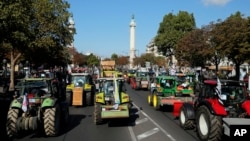 Angry farmers drive their tractors as they arrive in Paris, Sept. 3, 2015.