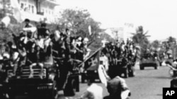 Flag-waving and jubilating Red Khmer soldiers enter the city of Phnom Penh on their trucks, April 17, 1975, when this Cambodian capital surrendered to the Khmer Rouge. Civilians pass the truck convoy on their motor scooters. (AP Photo)