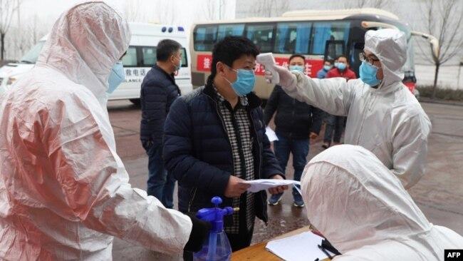 山东省邹平在公交车站设立检查点为来自河南的农民工测量体温。(2020年2月25日)