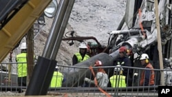 FILE - Rescue workers insert steel pipes to encase the escape tunnel used to free trapped miners at the San Jose mine near Copiapo, Chile, Oct. 10, 2010.