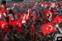 "FILE - In this Sunday, July 9, 2017, photo, supporters of Kemal Kilicdaroglu, the leader of Turkey's main opposition Republican People's Party, hold Turkish flags in Istanbul, as they gather for a rally following their 425-kilometer (265-mile) ""March for Justice."""