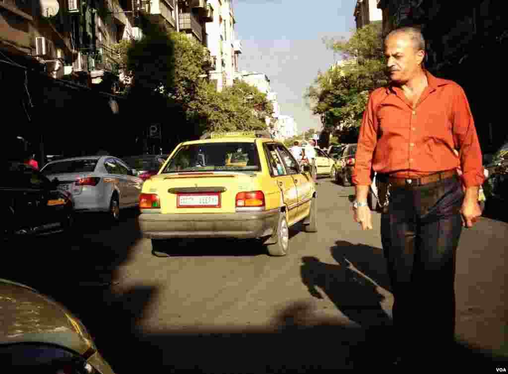 다마스쿠스 거리를 바쁘게 지나가는 한 남자. 일부 거리는 안전문제로 폐쇠됐다.