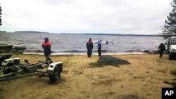 Para petugas penyelamat Rusia berada di lokasi tewasnya 14 anak peserta kamp musim panas di Danau Karelian, Rusia barat laut (19/6).
