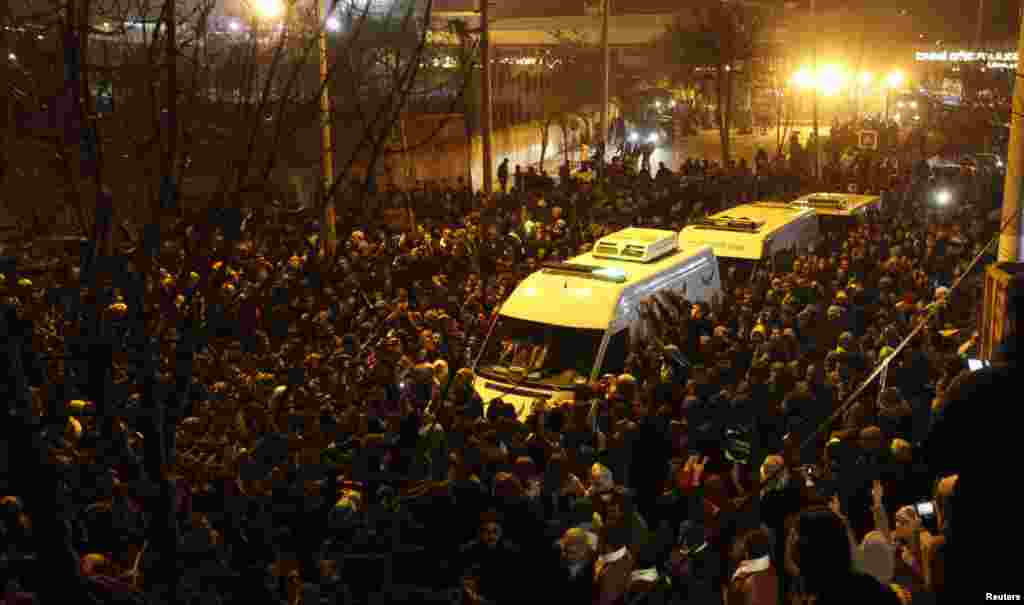 People accompany ambulances carrying the bodies of three Kurdish activists shot in Paris, in Diyarbakir, Turkey, January 16, 2013.