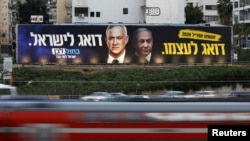 Kendaran melintas di depan poster kampanye pemilu partai Biru dan Putih dengan foto pemimpin partai Benny Gantz and Perdana Menteri Israel Benjamin Netanyahu di Tel Aviv, Israel, 18 Februari 2020. (Foto: Reuters)