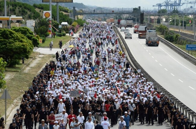 """FILE - Kemal Kilicdaroglu, the leader of Turkey's main opposition Republican People's Party, walks with thousands of supporters on the 21st day of his 425-kilometer (265-mile) """" March for justice """" in Izmit, Turkey, July 5, 2017."""
