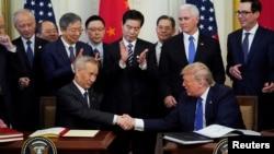 """Le vice-Premier ministre chinois Liu He et le président américain Donald Trump se serrent la main après avoir signé la """"phase 1"""" de l'accord commercial américano-chinois à Washington, États-Unis, le 15 janvier 2020. REUTERS / Kevin Lamarque"""