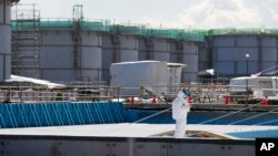FILE - A worker, wearing protective suits and masks, takes notes in front of storage tanks for radioactive water at the tsunami-crippled Fukushima Dai-ichi nuclear power plant, operated by Tokyo Electric Power Co. (TEPCO), in Okuma, Fukushima Prefecture, northeastern Japan. To dump or not to dump a little-discussed substance is the question brewing in Japan as it grapples with the aftermath of the nuclear catastrophe in Fukushima five years ago. The substance is tritium, Feb. 10, 2016.