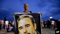 Seorang perempuan memegang foto Fidel Castro untuk menghormati pemimpin Kuba itu di lapangan Antonio Maceo di Santiago, Kuba, Sabtu, 3 Desember 2016.