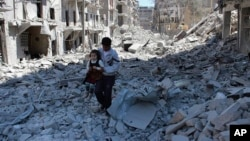 FILE - A Syrian man holds a girl as he stands on the rubble of houses that were destroyed by Syrian government forces air strikes in Aleppo, Syria, on April 21, 2014. The French foreign minister says Russia could face war crimes for its bombing campaign of Aleppo.