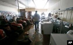 Paul Raines walks through his flooded Western Auto store in Rainelle, W.Va., June 25, 2016.