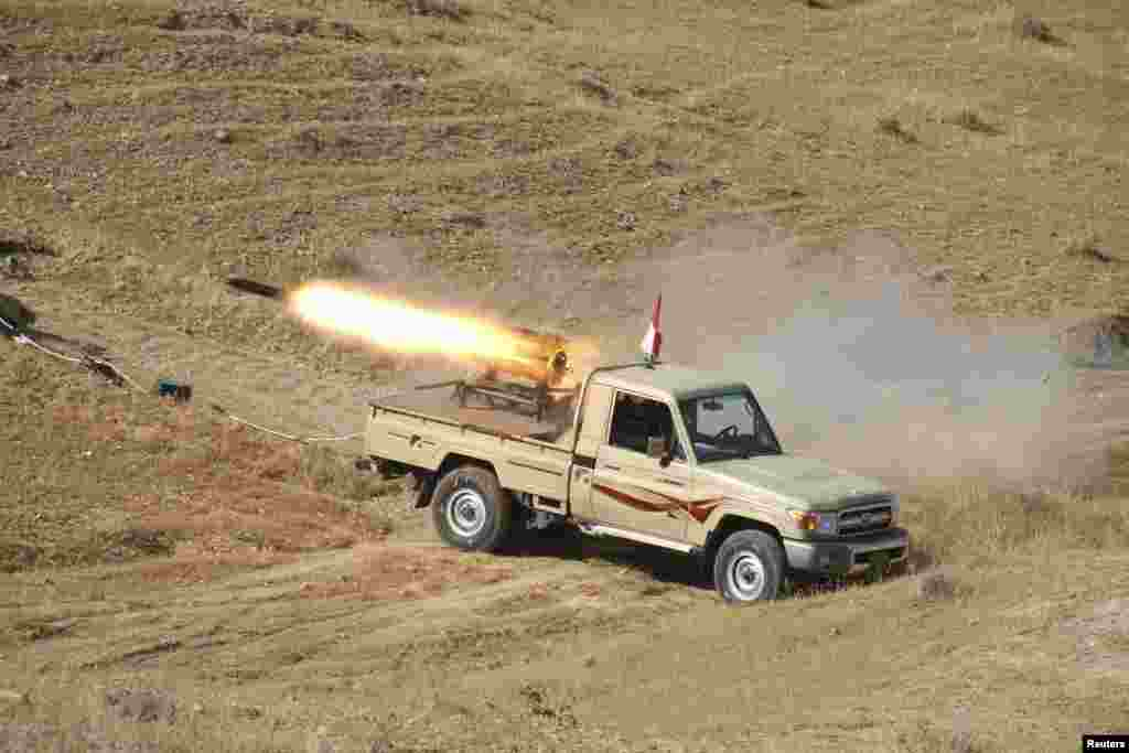 A vehicle belonging to Kurdish security forces fires a multiple rocket launcher during clashes with the Islamic State of Iraq and the Levant on the outskirts of Diyala, Iraq, June 14, 2014.