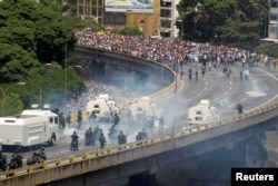 "FILE - Demonstrators clash with riot police during the so-called ""mother of all marches"" against Venezuela's President Nicolas Maduro in Caracas, Venezuela, April 19, 2017."