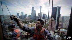2018年6月8日,在北京壮观的中央商务区,中国工人在悬浮平台上清洁办公大楼的窗户。