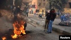 Para pendukung Ikhwanul Muslimin dan presiden Mesir tersingkir Mohamed Mursi menutup jalan dalam bentrokan dengan polisi di Kairo (25/1). (Reuters/Mohamed Abd El Ghany)