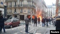 Warga berkumpul di dekat sebuah toko roti di mana ledakan yang diduga akibat ledakan gas terjadi di Paris, Perancis (12/1).
